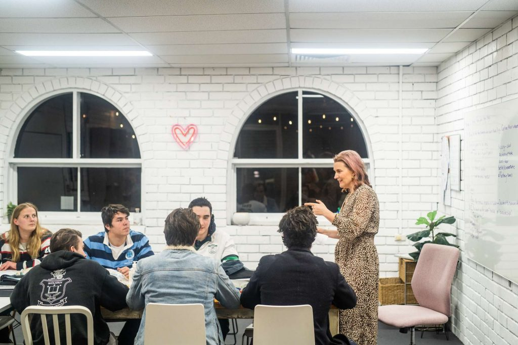 About Clever Cookie Academy - photo of Peita Mages teaching a classroom of high school students.