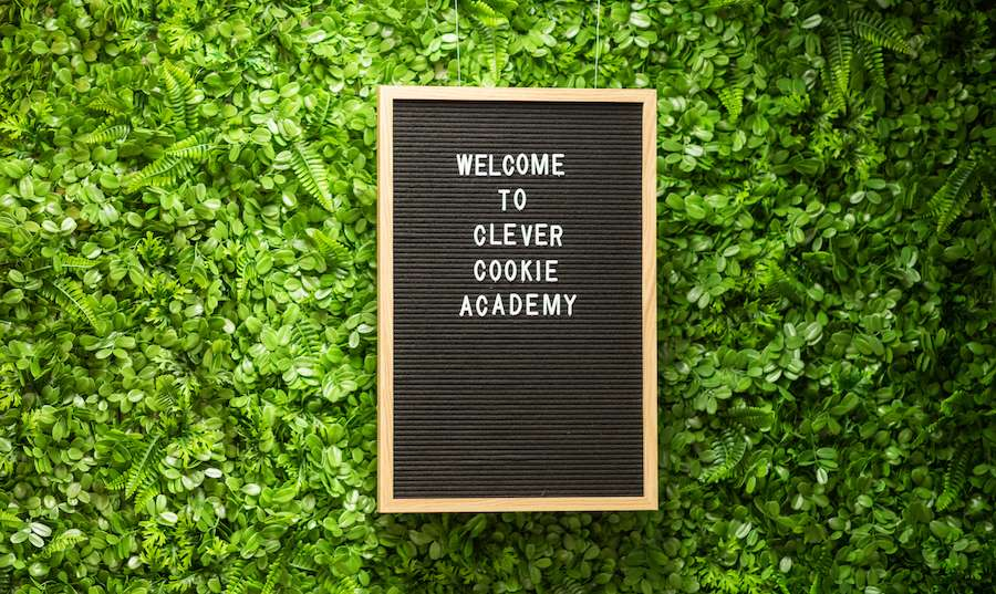 """Sign saying """"Welcome to Clever Cookie Academy"""" against a green decal wall."""