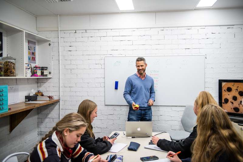 Photo of Rob Mages, Clever Cookie Academy co-founder, teaching a classroom of high school students.